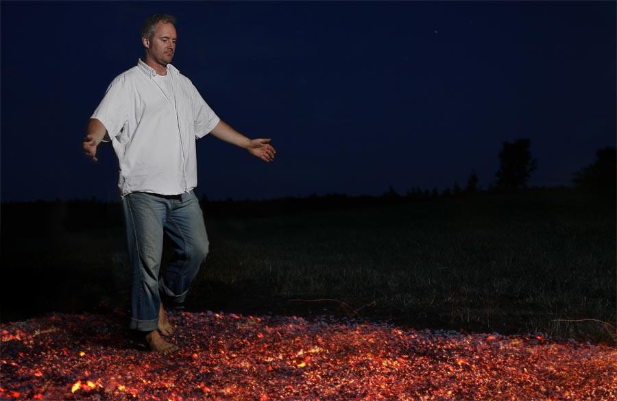 Feuerlauftrainer Rolf Iven geht barfuß über glühende Kohlen